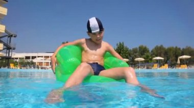 Boy sitting on inflatable chair in the pool water — Stock Video