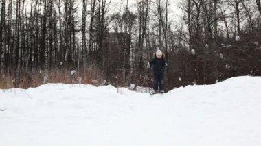 Jonge jongen dia neer op ski's van snow hill — Stockvideo