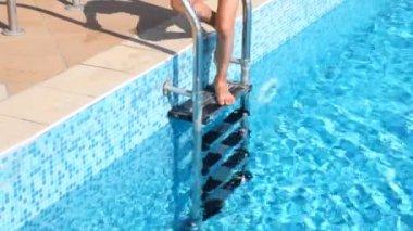 Menino na touca desce na água da piscina — Vídeo Stock