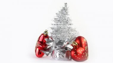 Silver artificial Christmas tree made of tinsel grows from gift wrapping rotate, near lie red Christmas tree star and heart — Stock Video