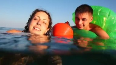 Girl and boy in inflatable disc is afraid, cannot swim, cling buoy into sea — Stock Video