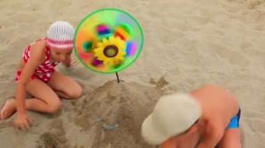 Children make a mound of sand, where the set toy that spins — Stock Video