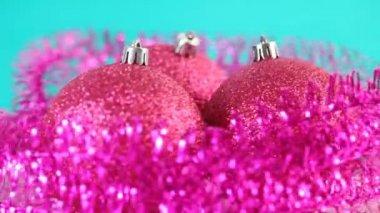 Drie roze kerstboom ballen roteren, omgeven door paarse klatergoud op blauwe achtergrond — Stockvideo