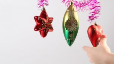 Christmas-tree decoration swing on tinsel, childrens hand touches it — Stock Video