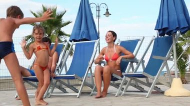 Parents are sitting in deckchairs, and kids dancing in front of them — Stock Video
