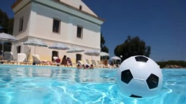 Small inflatable soccer ball floats in the pool — Stock Video