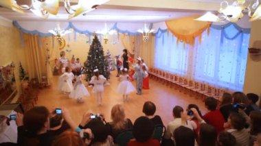 Children dance about an christmas fir-tree in kindergarten — Stock Video