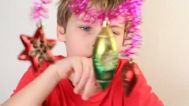 Boy play with christmas-tree decoration. — Stock Video