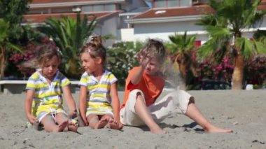 Två barn sitter på sanden och kasta dem mot huset — Stockvideo