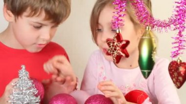 Girl and boy play with christmas-tree decoration — Stock Video