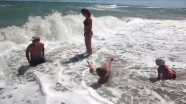 Parents and children wallowing in the sea waves rollsed — Stock Video