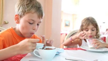 Boy and girl eat granola and yogurt for breakfast — Stock Video