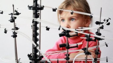 Dziewczynki patrzeć na super konstrukcja z dwóch kulek toczenia przez — Wideo stockowe
