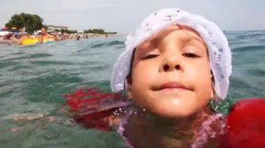 Little girl in inflatable arm ruffles swims at sea — Stock Video