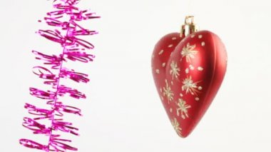 Red Christmas tree star and heart swing on purple tinsel on white — Stock Video