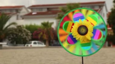 Round toy with sunflower in the center is set in the ground and spinning — Stock Video