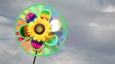Toy with sunflower in center, that spins on the background of sky — Stock Video