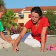 Mother and her kids sitting on sand, made sand pile — Stock Video