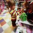 Stock Video: Little girl carefully choose toy in shop