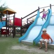 Two children are on playground object, boy sliding down — Stock Video