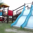 Two children are on playground object, both slide down — Stock Video #28805957