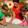 Mother and her kids sitting on sand and writing on it — Vídeo de stock