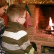 Two sons and father sitting near fireplace — Stock Video