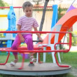 Little girl sitting on carousel and rotating it by leg — Stock Video #28806241