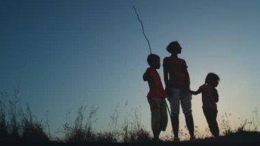 матери и дети, стоя на холме, мальчик, холдинг длинные тонкие палки — Стоковое видео