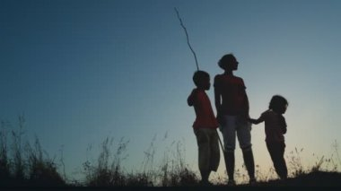 Madre e hijos está en colina, niño con palo largo y fino — Vídeo de stock
