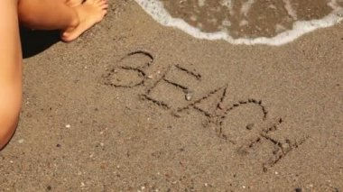 La playa de palabra está escrita en la arena, ola de mar aparecen — Vídeo de stock