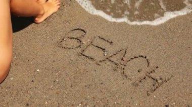 Ordet stranden är skriven på sanden, havet wave visas — Stockvideo