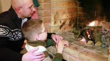 Padre e hijo sentados junto a la chimenea — Vídeo de stock