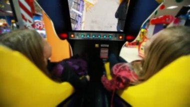 Two girls watch film on motion simulator, screen movie with roller coaster — Stock Video