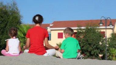 Mutter und ihre kinder auf sand sitzen und meditieren — Stockvideo