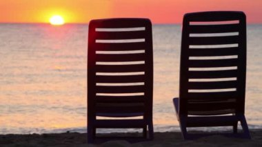 Seascape at evening sunset shown behind two deckchairs — Stock Video
