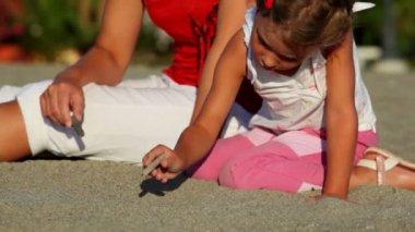 Mor och hennes dotter som sitter på sand och flickan teckning på den av pinnar — Stockvideo
