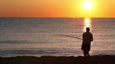L'homme jette une canne à pêche et fait ensuite signe poissons — Vidéo