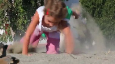 Two kids grabble by sand kicking up dust — Stock Video