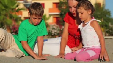 母亲和孩子们坐在沙滩上和孩子们的棍子在它上面绘制 — 图库视频影像