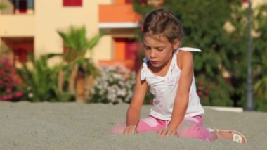 Little girl sitting on sand and writing on it — Stock Video