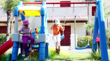 Two kids on playground, boy is sways on swing girl went out — Stock Video