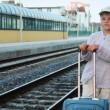 Boy with travel bag stands and smiles on train station near railway lines — Stock Video #28811395