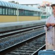 Boy with travel bag stands on train station near railway lines — Stock Video #28811515