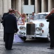 Stock Video: Photographing newlyweds near old car on square in front St. Peters Basilica