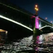 Stock Video: Camermoves at night under lighted iron bridge standing on Neva