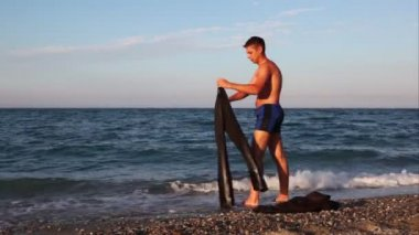 Man standing on beach and washing suit pants in sea — Stock Video