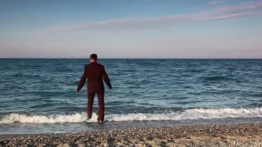 Man standing on beach, then going and immersed to sea water — Stock Video