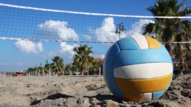 Ball lies on sand under volleyball net at beach near palm trees — Stock Video