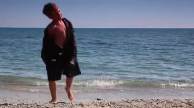 Boy going out sea water and put off suit jacket — Stock Video